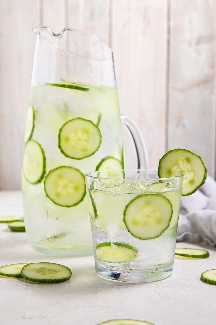 Pitcher and glass filled with cucumber water