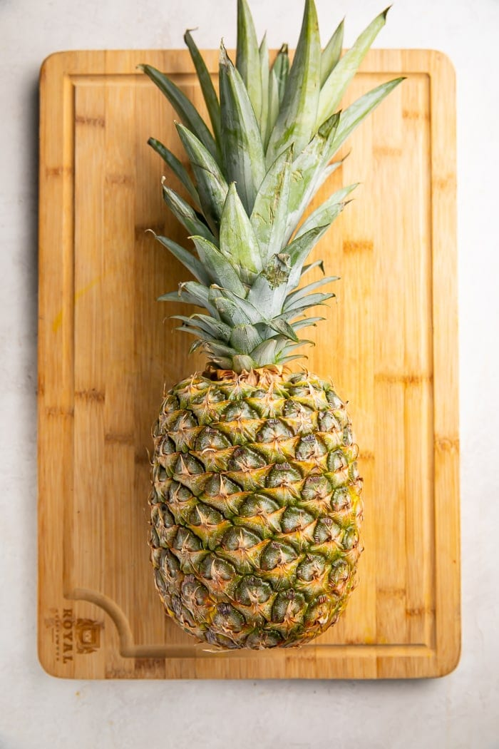 A whole pineapple lying on a cutting board