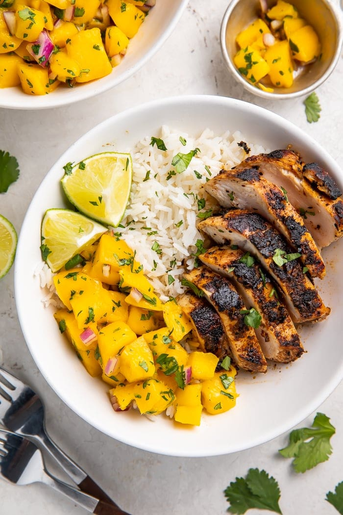 Overhead of jerk chicken bowl with coconut rice and mango salsa