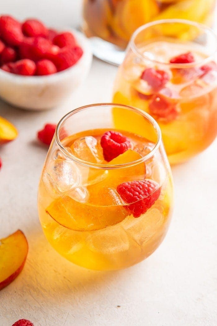 White wine sangria with peaches and raspberries in a glass