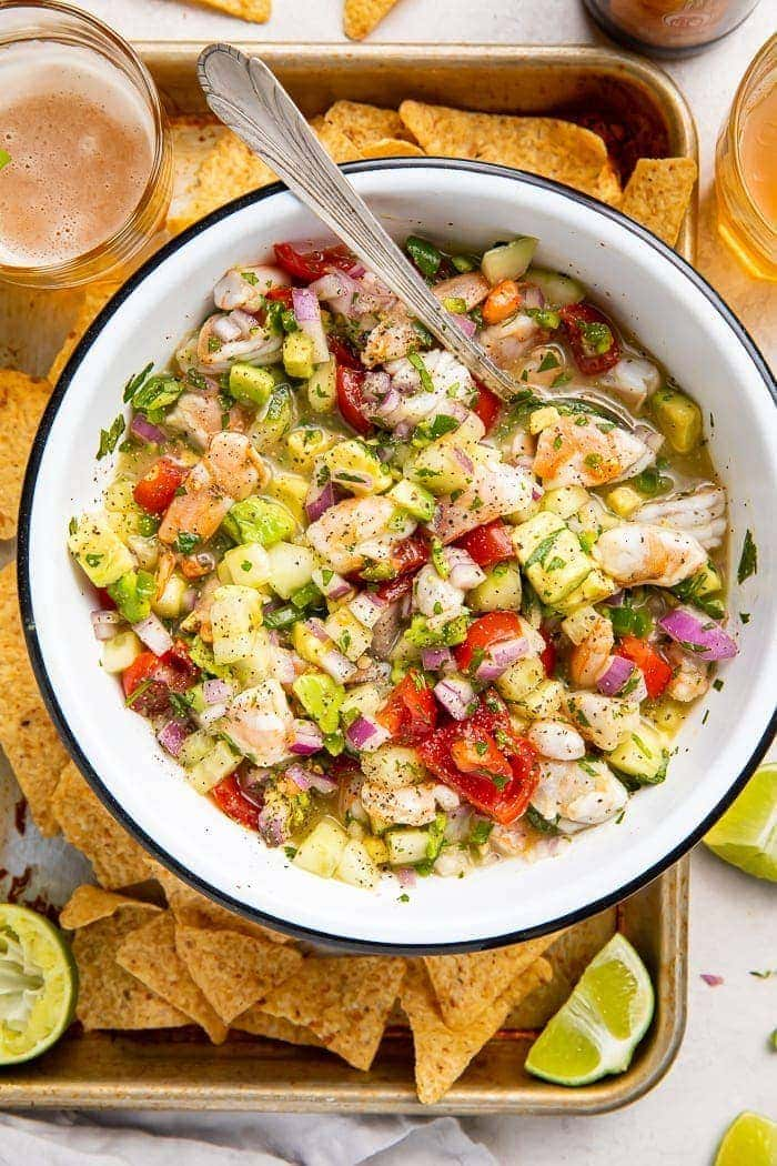 Shrimp ceviche in a bowl with chips and lime wedges