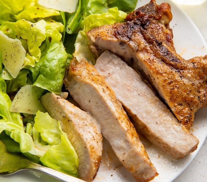 Sliced pork chop cooked in the air fryer with a bed of green veggies on a white plate