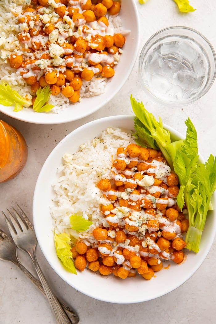 Two bowls of buffalo chickpeas with ranch on a bed of white rice and celery tops