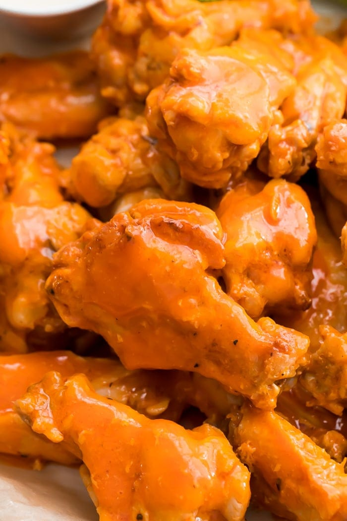 close-up of a pile of fried chicken wings smothered in buffalo sauce