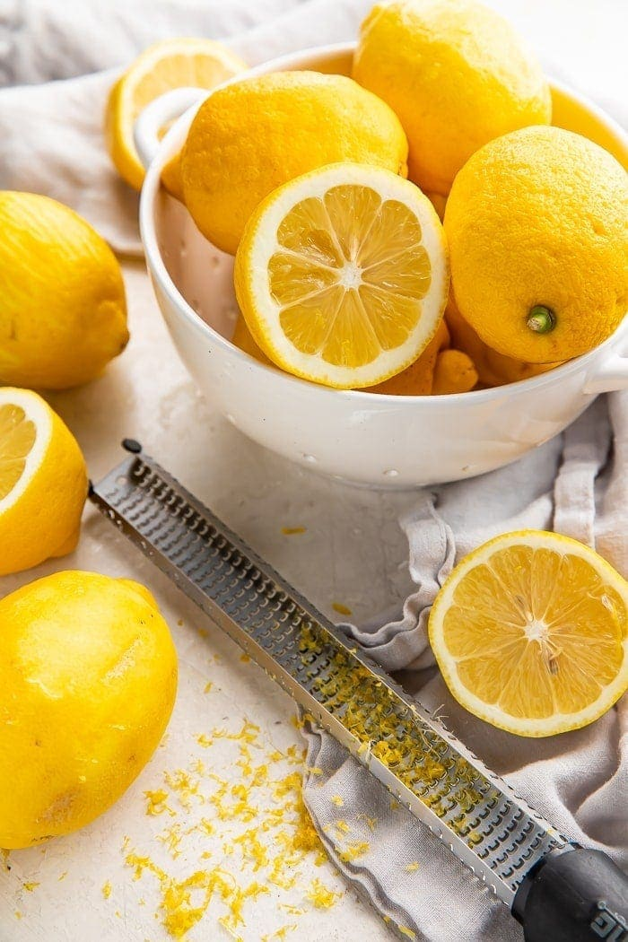 a bowl of lemons surrounded by sliced lemons, a microplane, and lemon zest