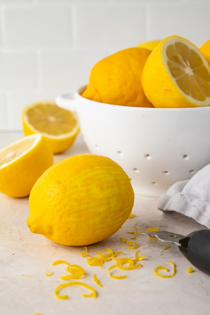 a zested lemon surrounded by lemon zest, a zester, and a colander of lemons