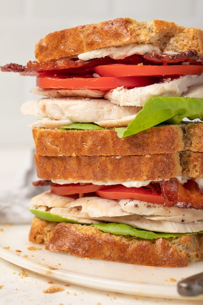 Turkey, lettuce, bacon, and tomato sandwiches made from paleo bread stacked on top of each other
