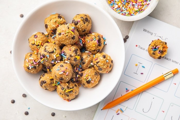 peanut butter and chocolate chip energy balls in a white bowl with sprinkles