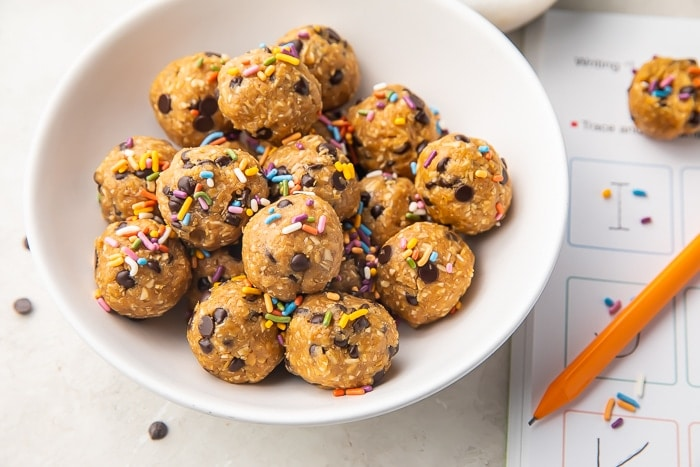 peanut butter and chocolate chip energy balls in a white bowl with sprinkes