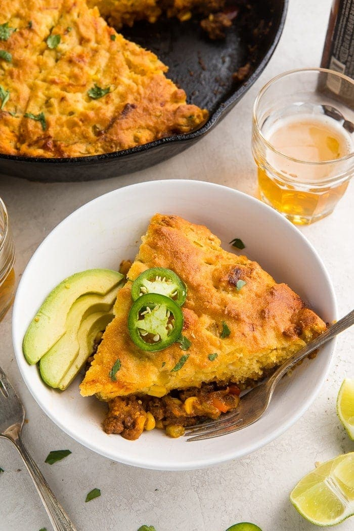 Slice of tamale pie garnished with avocado slices and jalapeño on a plate