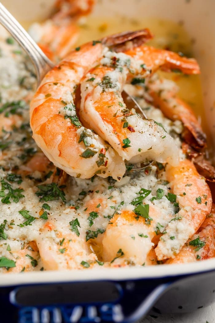 Baked shrimp being spooned out of a baking dish