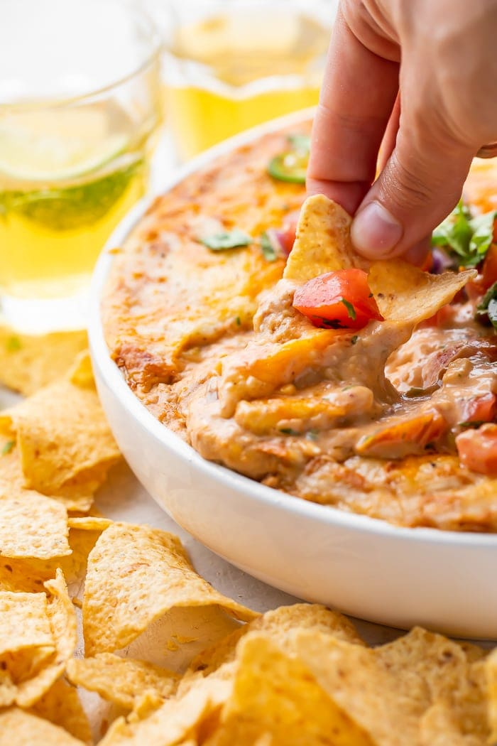 A hand dipping a corn chip into a bowl of bean dip in a bowl surrounded by glasses of beer and more chips