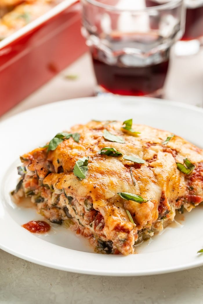 A slice of eggplant lasagna on a white plate with a glass of red wine in the background