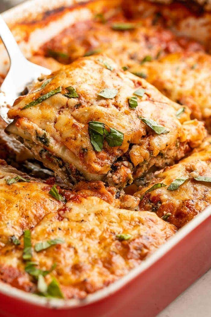 A slice of eggplant lasagna being lifted from a baking dish
