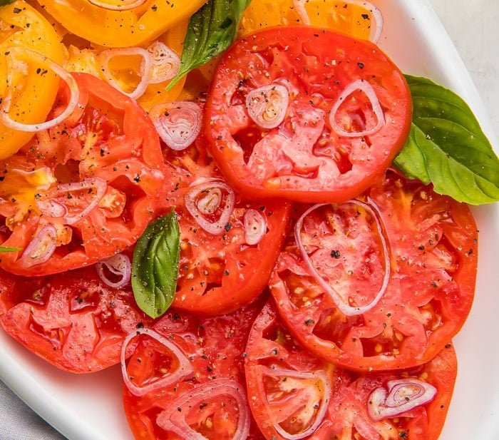Red and yellow heirloom tomatoes on a serving plate with slices shallots and basil leaves