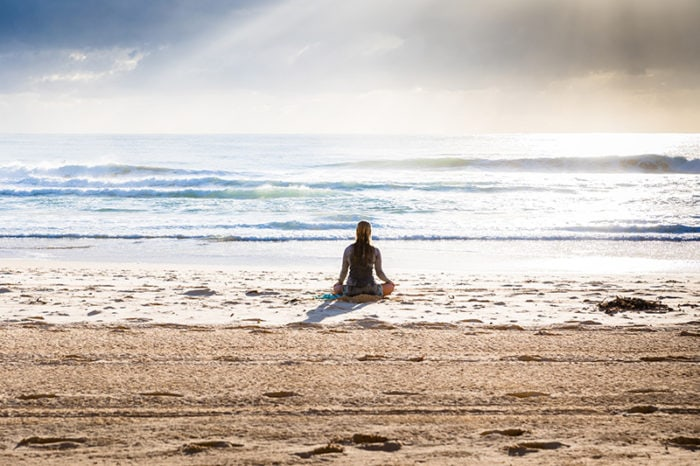 Woman meditating on the beach by the ocean