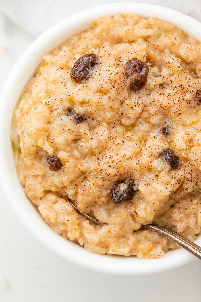 Overhead shot of rice pudding with raisins, sprinkled with cinnamon, with a spoon