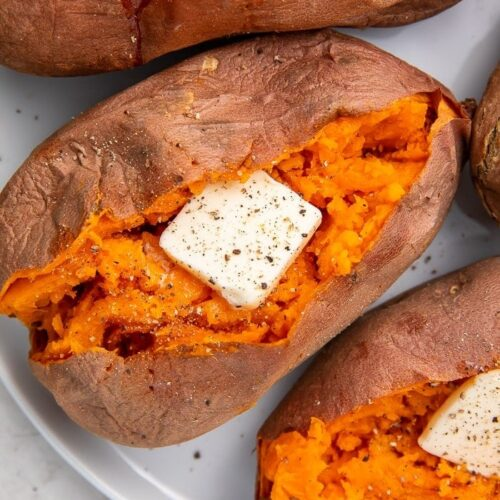 Close up of sweet potatoes cut open and stuffed with butter, salt, and pepper, on a white plate