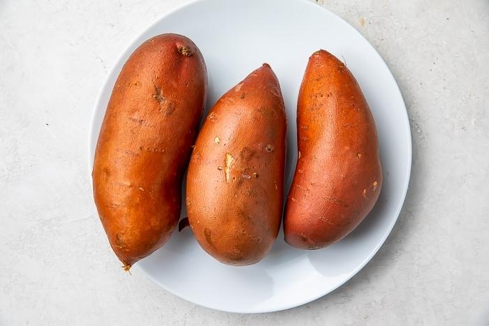 Three sweet potatoes on a white plate