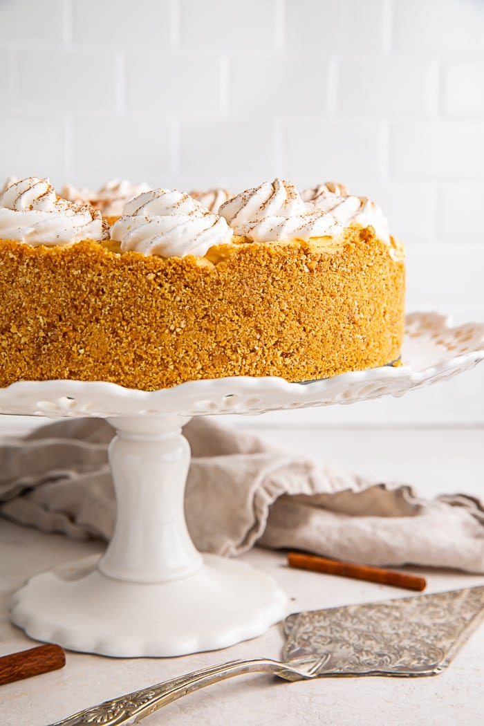 A pumpkin cheesecake on a white cake stand