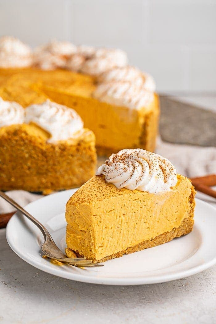 A slice of no bake pumpkin cheesecake on a white plate with a cheesecake in the background