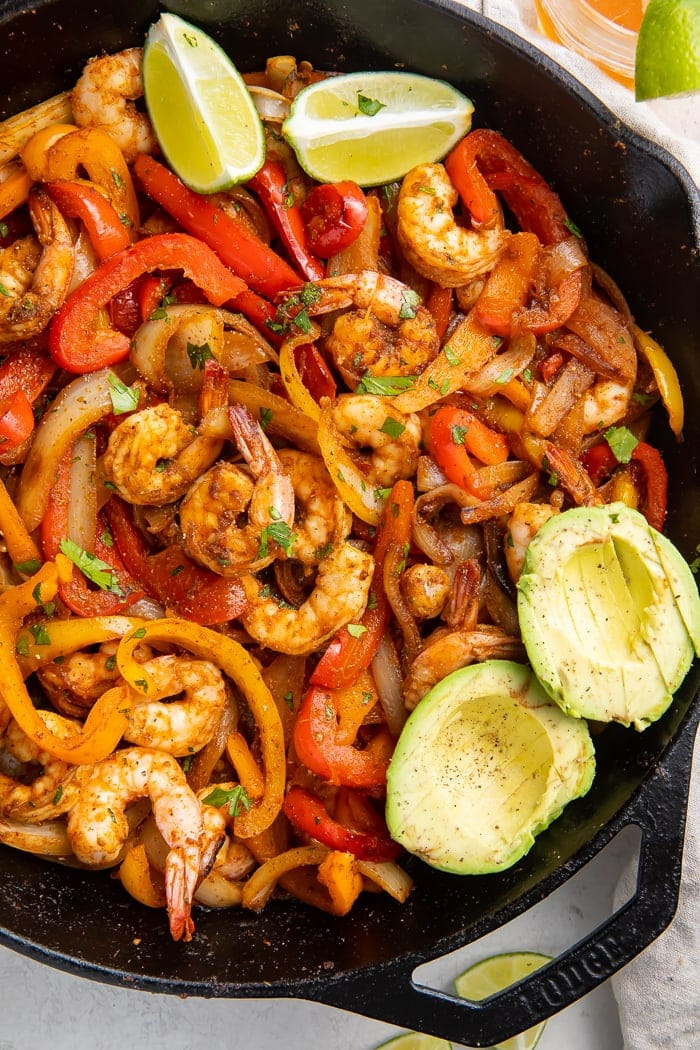 Shrimp, bell peppers, and other ingredients for shrimp fajitas in a cast iron skillet along with two halves of avocados and two lime wedges