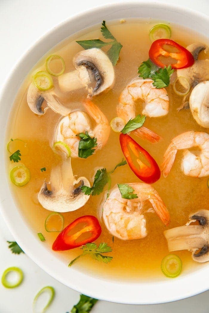 Tom yum soup in a bowl with shrimp, chilis, mushrooms, and pieces of green onion and cilantro