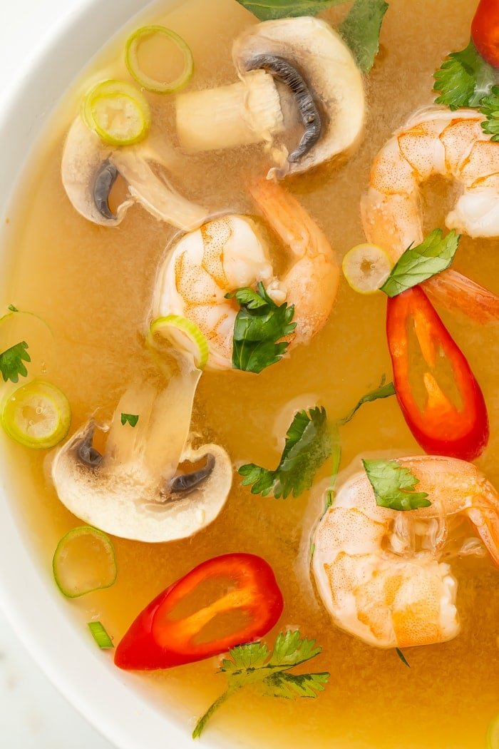 Close-up of tom yum soup in a bowl with shrimp, chilis, mushrooms, and pieces of green onion and cilantro