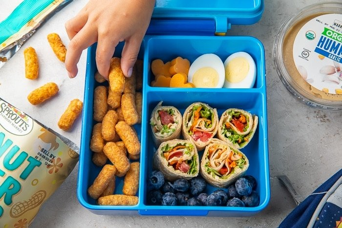 Child's hand reaching into a bento lunchbox filled with vegetarian snacks