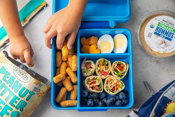 Children's hands reaching for food in vegetarian bento lunchbox