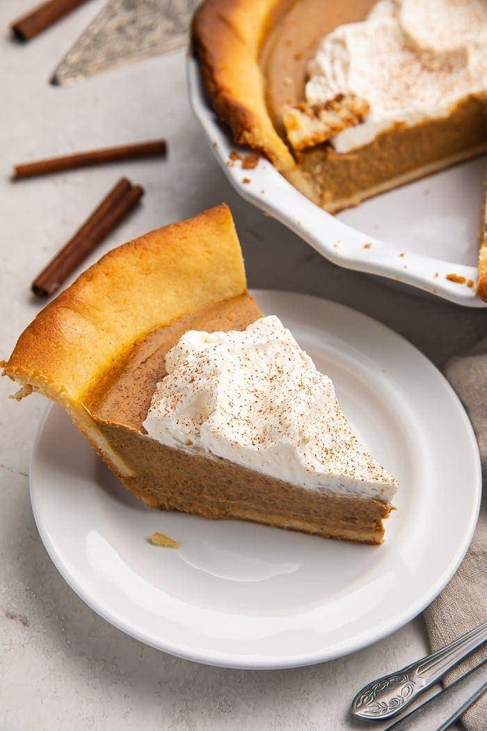 A slice of keto pumpkin pie topped with whipped cream on a white plate with a pie in the background