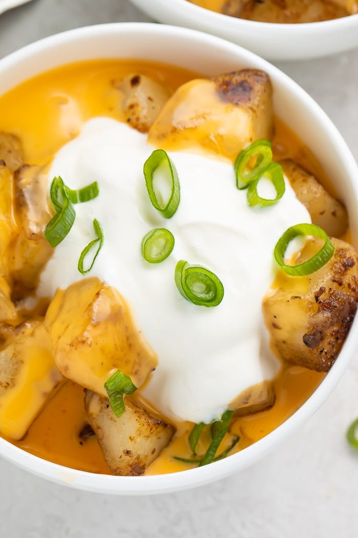 Close-up of cheesy fiesta potatoes in a bowl with a dollop of sour cream and sliced green onions