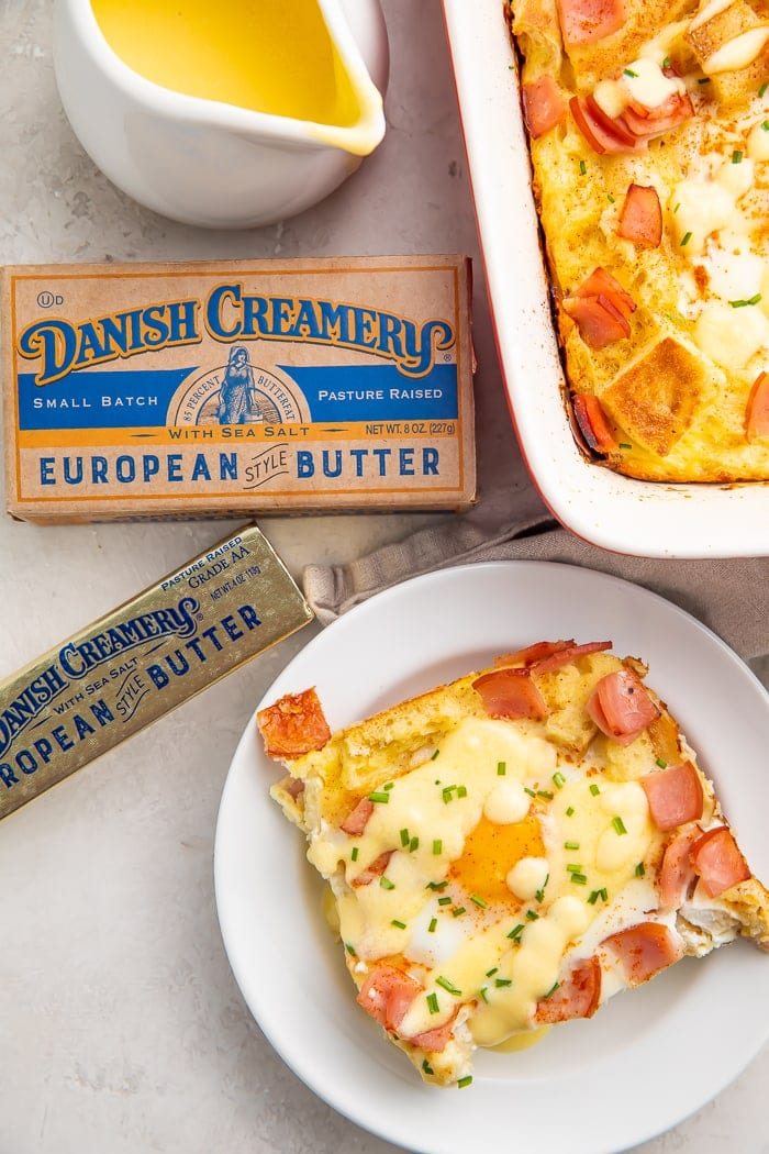 A slice of eggs benedict casserole on a white plate surrounded by a stick of Danish Creamery butter and a kraft box of butter