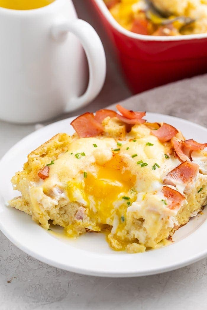 A slice of eggs benedict casserole with a bite taken out on a white plate with a mug and red bowl in the background