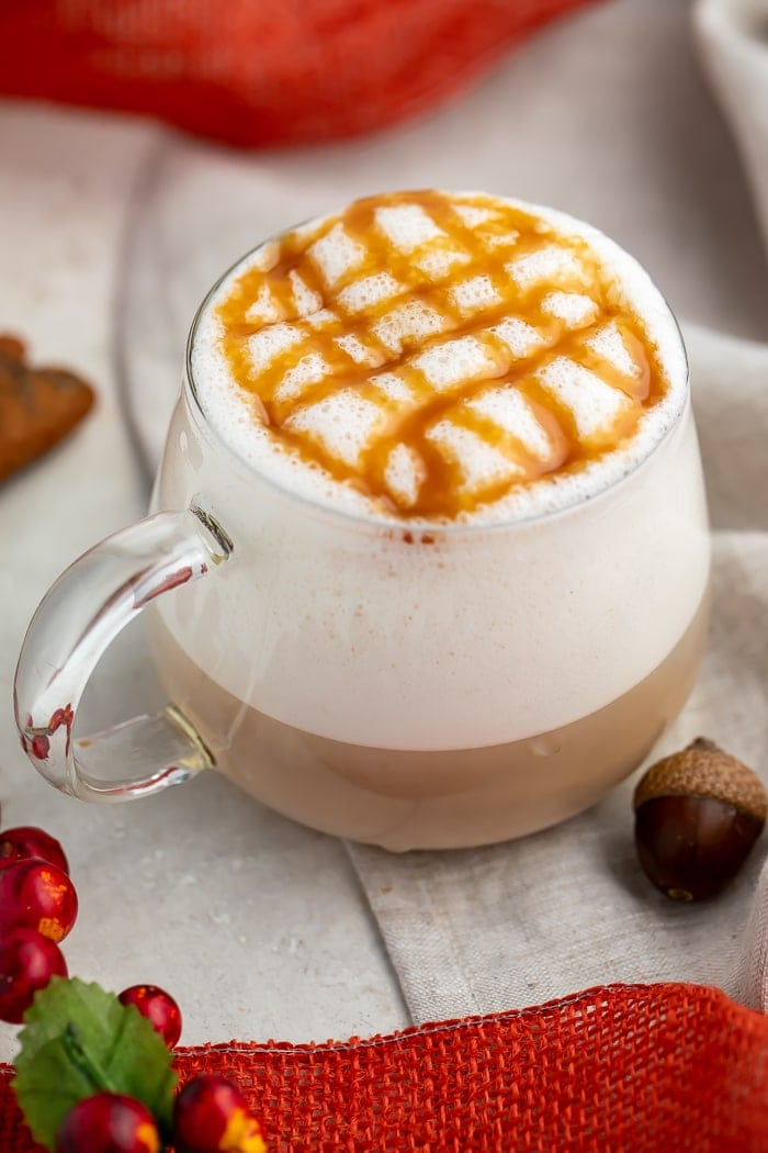 A glass mug of pumpkin caramel macchiato with lots of froth and a criss-cross design made of caramel sauce on the top
