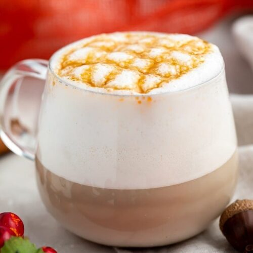 White coffee mug with coffee, whipped cream, and caramel cross-stitch drizzle