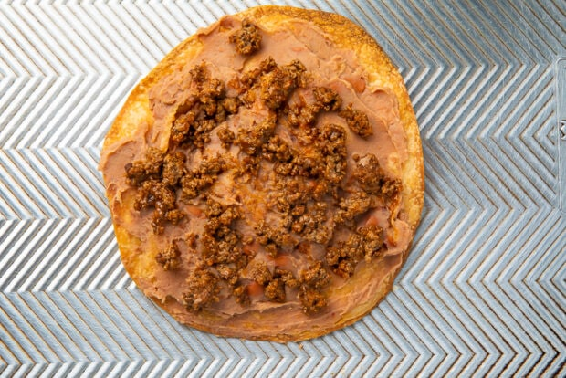 Ground beef and refried beans spread on a baking tortilla