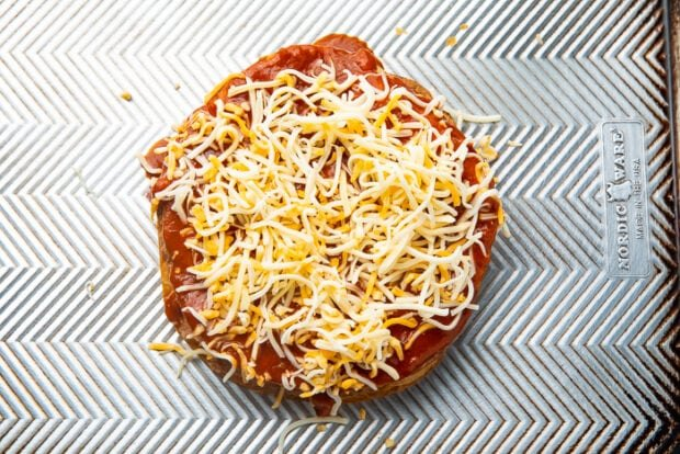 Shredded cheese on top of a Mexican pizza that has not been cooked yet
