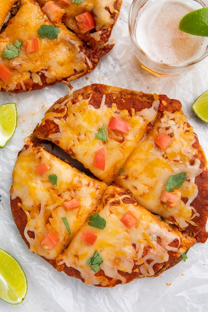 Overhead shot of Taco Bell Mexican pizza recipe topped with diced tomatoes and cilantro cut into four slices, surrounded by a lime wedge, glass of beer, and a bottle cap