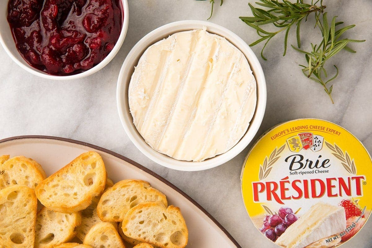 Ingredients for cranberry brie dip on a white tablecloth next to a serving dish of crostini