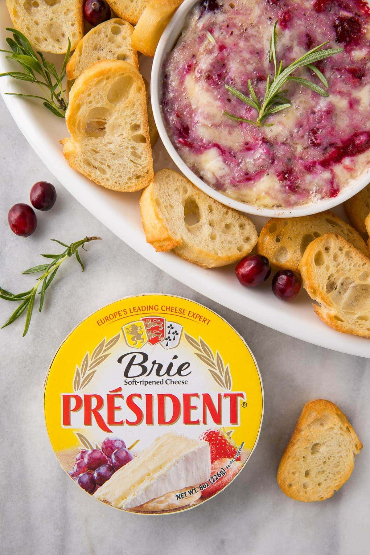 A serving tray with crackers and cranberry brie dip with a package of President Brie