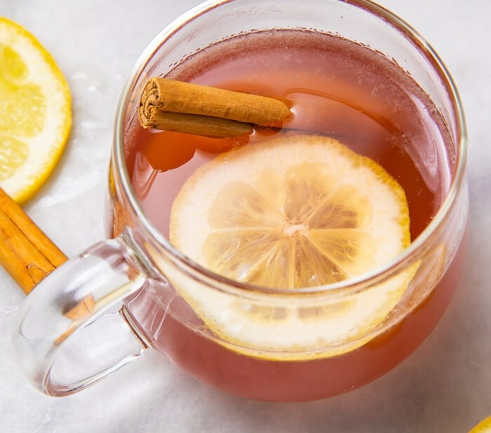 Overhead shot of elderberry hot toddy with lemon and cinnamon stick