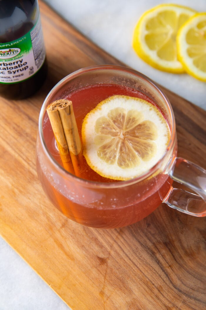 Elderberry hot toddy on a wooden plank next to lemon slices and a bottle of elderberry syrup