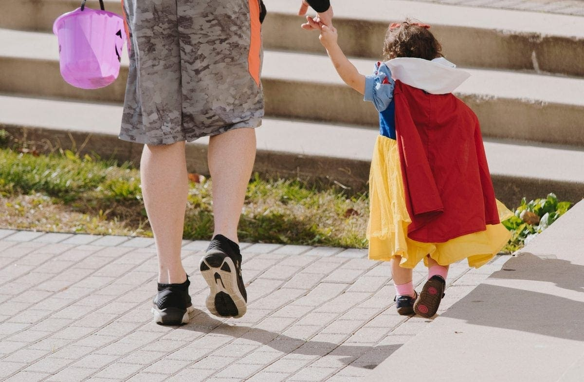 Woman trick-or-treating with little girl dressed as Snow White