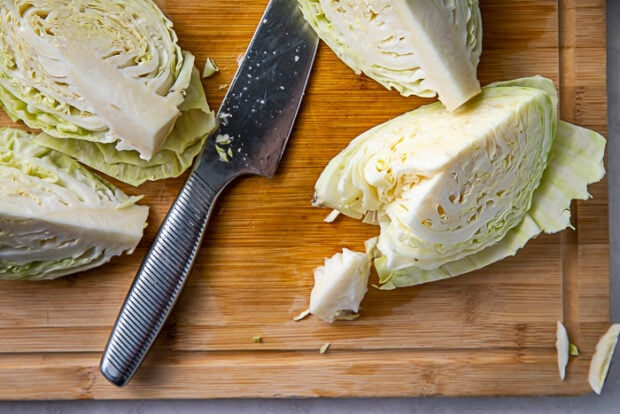 Four wedges of a head of cabbage on a cutting board next to a knife