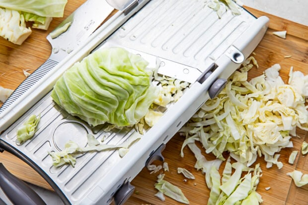 Mandolin with a wedge of cabbage on top and shredded cabbage on a cutting board