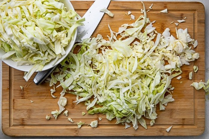 Shredded cabbage on a wooden cutting board next to a knife
