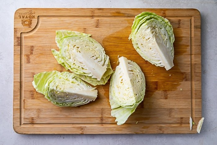 Four wedges of a head of cabbage on a wooden cutting board