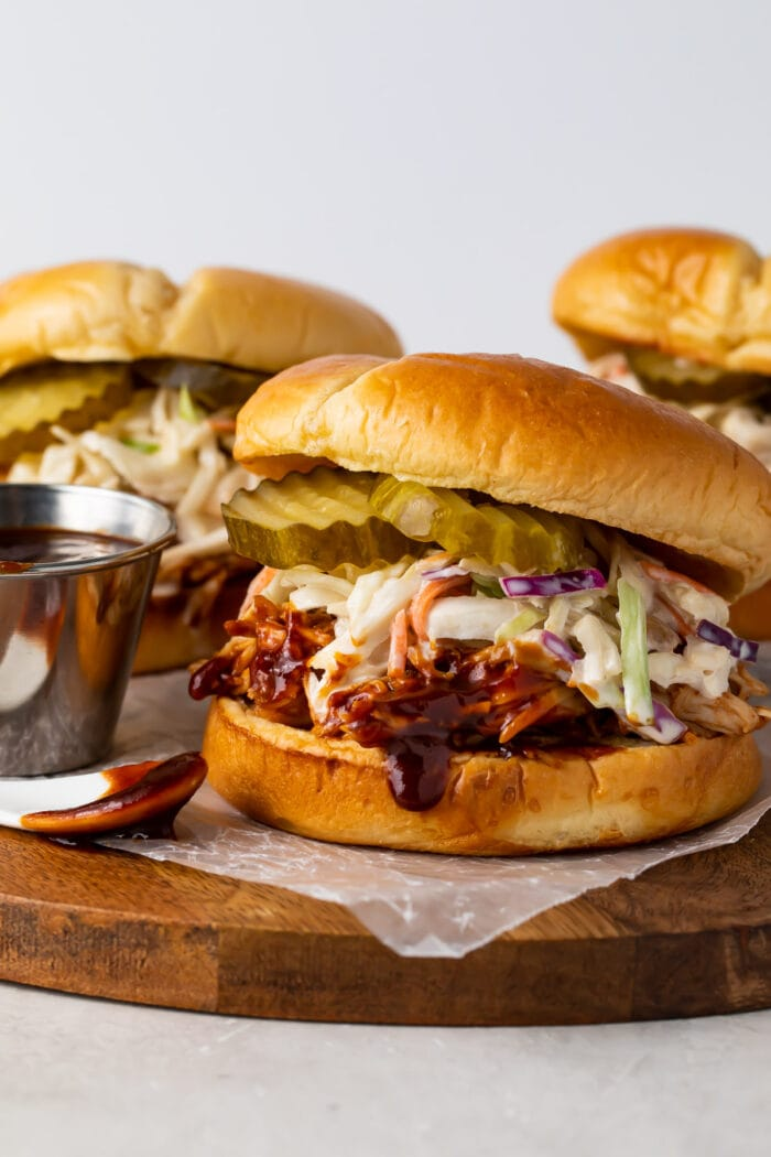 Three Instant Pot BBQ chicken sandwiches wit coleslaw and pickles