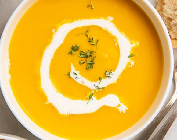 A bowl of butternut squash soup with a drizzle of cream inside a white bowl